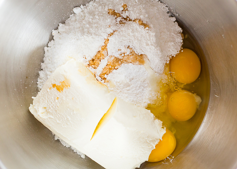 cream cheese, eggs, and powdered sugar in a bowl