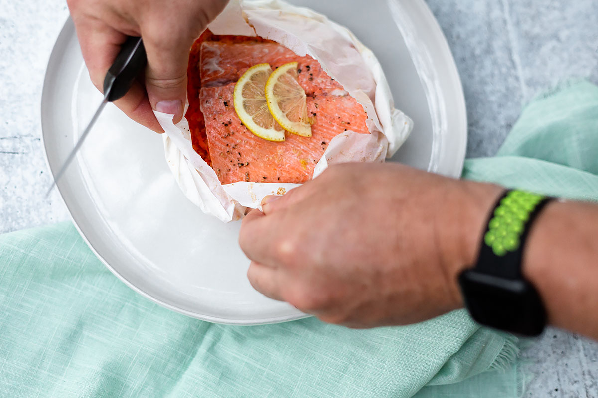 tearing open salmon in parchment