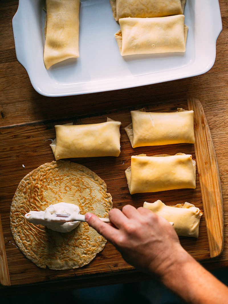 adding the cheese mixture to blintzes