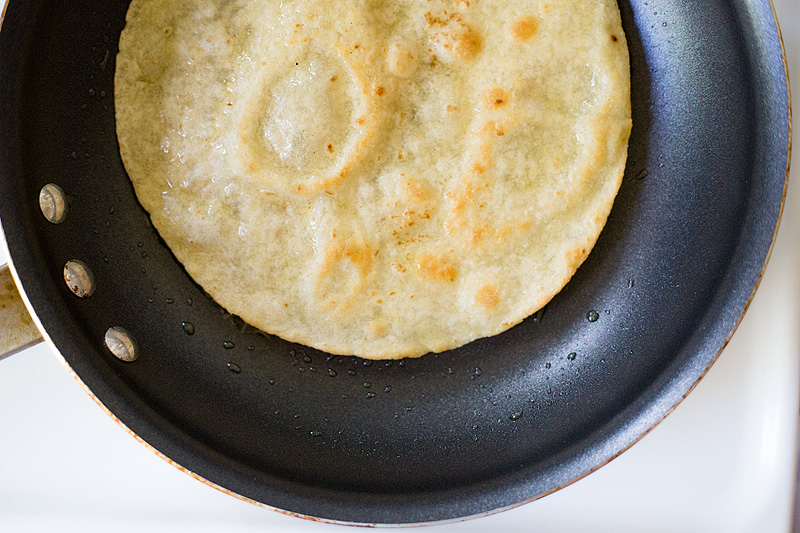 frying a tortilla in a skillet