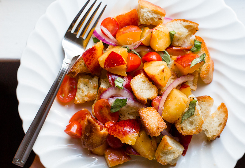 peach panzanella salad with tomatoes up close on a plate