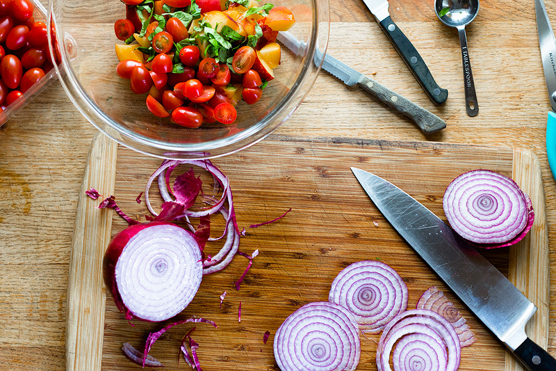 peaches, tomatoes and basil in a bowl with sliced red onion