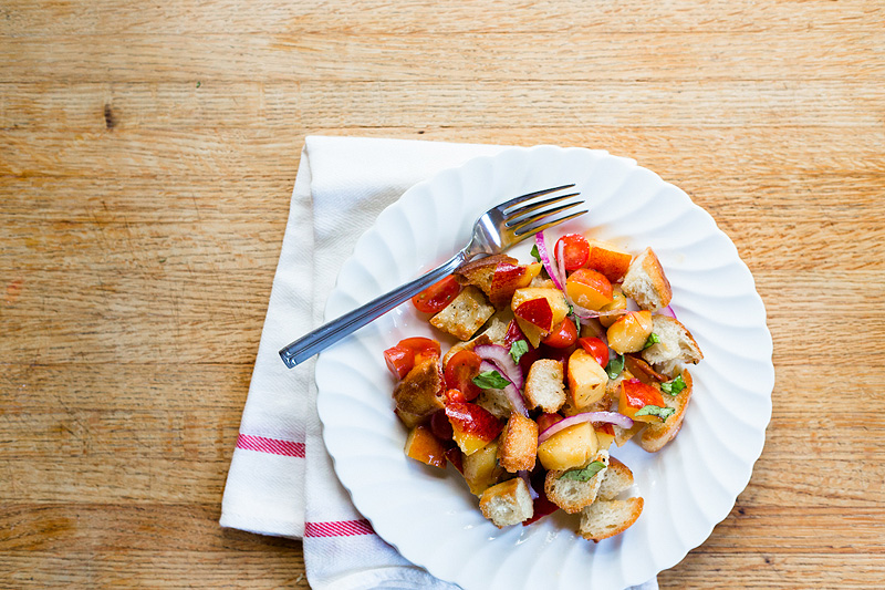 peach panzanella with tomatoes on a plate top down