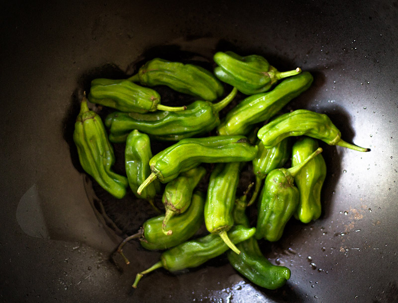 Blistered Shishito Peppers cooking in a wok