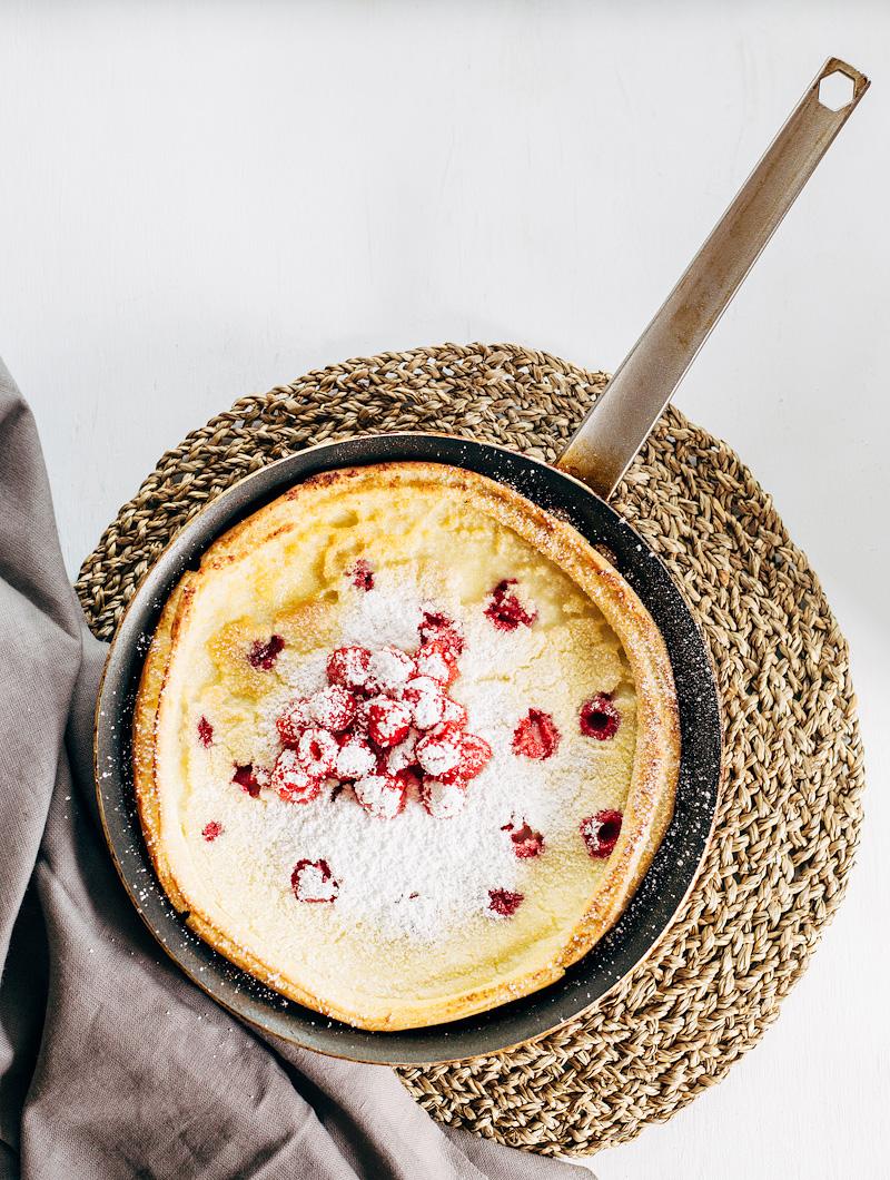 Raspberry Dutch Baby Pancake with fresh raspberries and powdered sugar