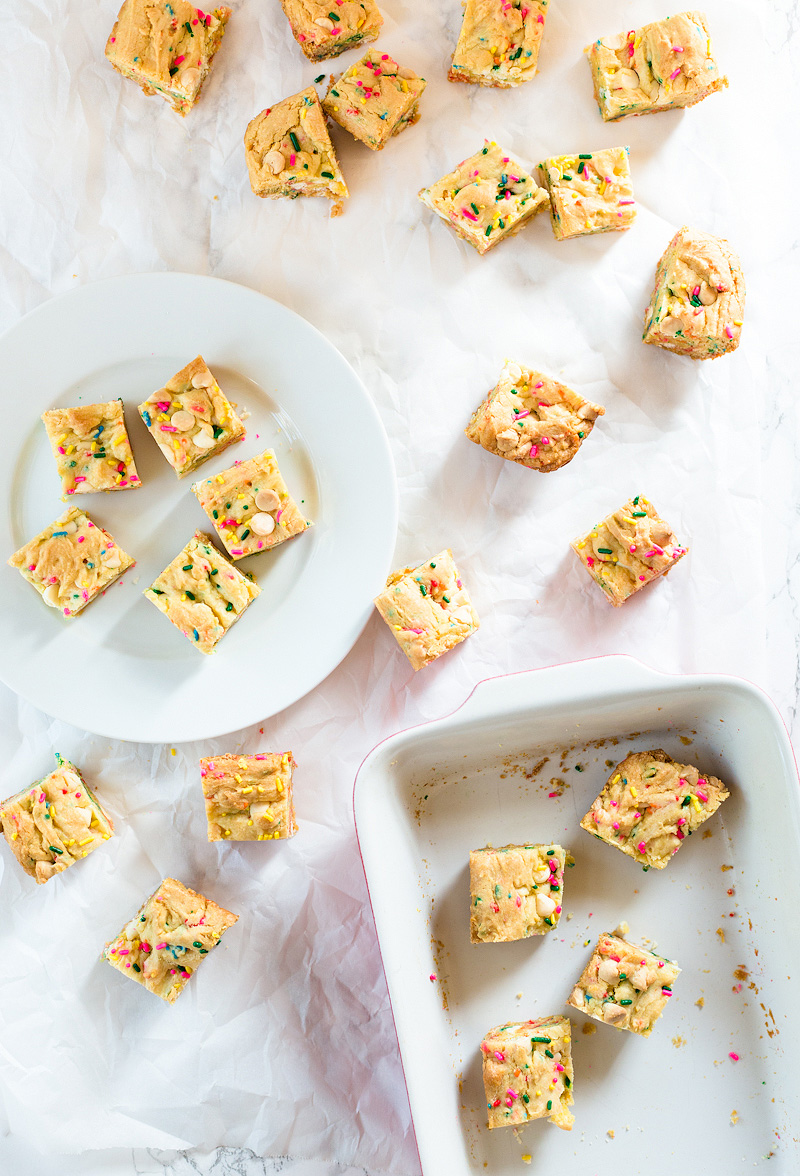 Gooey Confetti Cake Bars cut and spread out over parchment paper