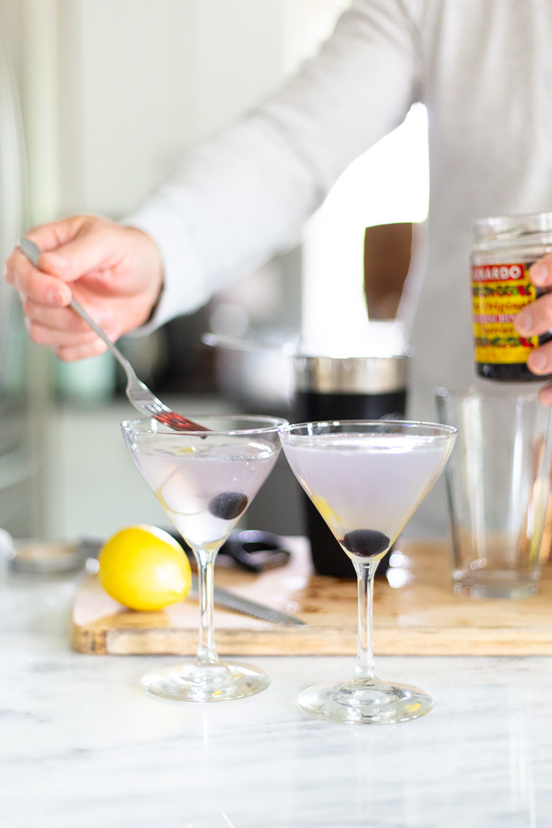 adding cherries to an aviation cocktail