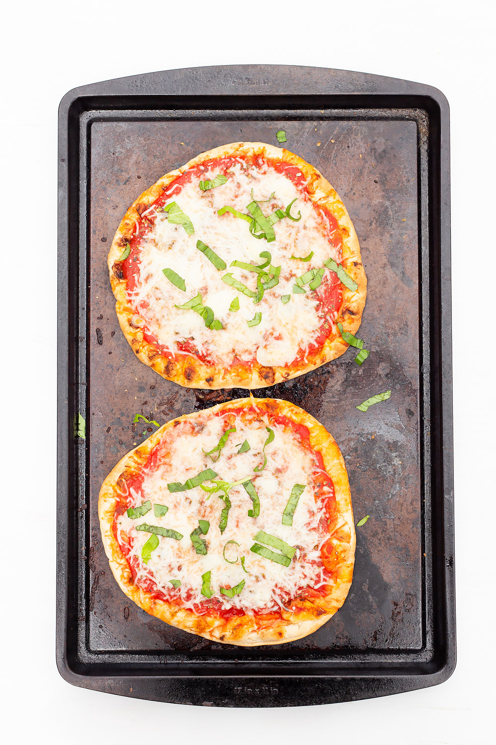 naan pizzas on a cookie sheet