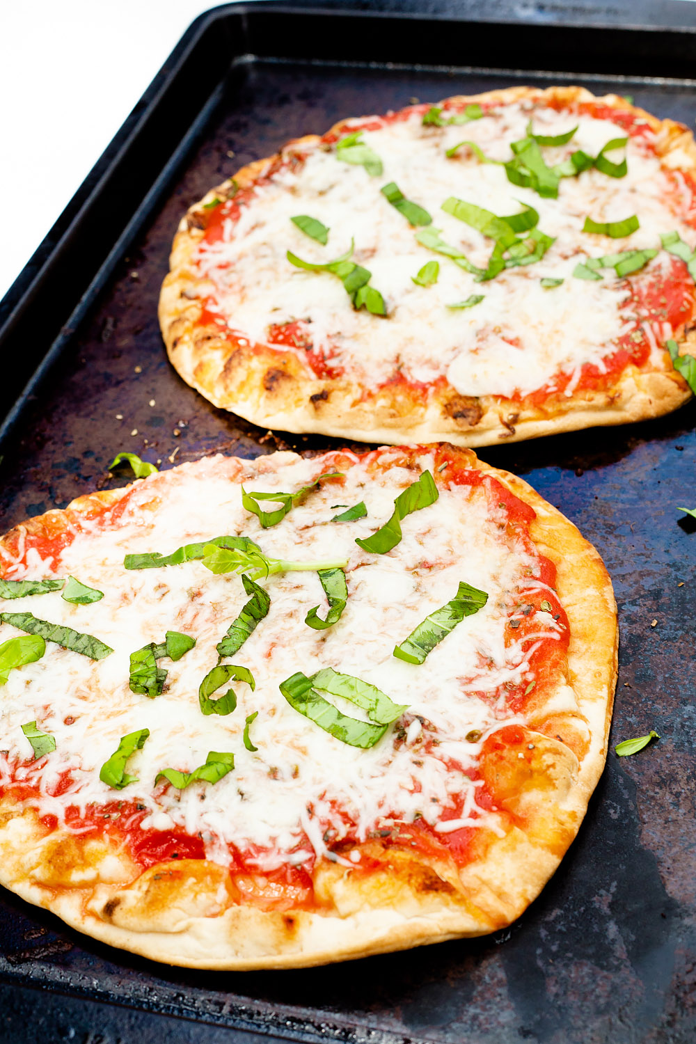 naan pizzas with basil on top