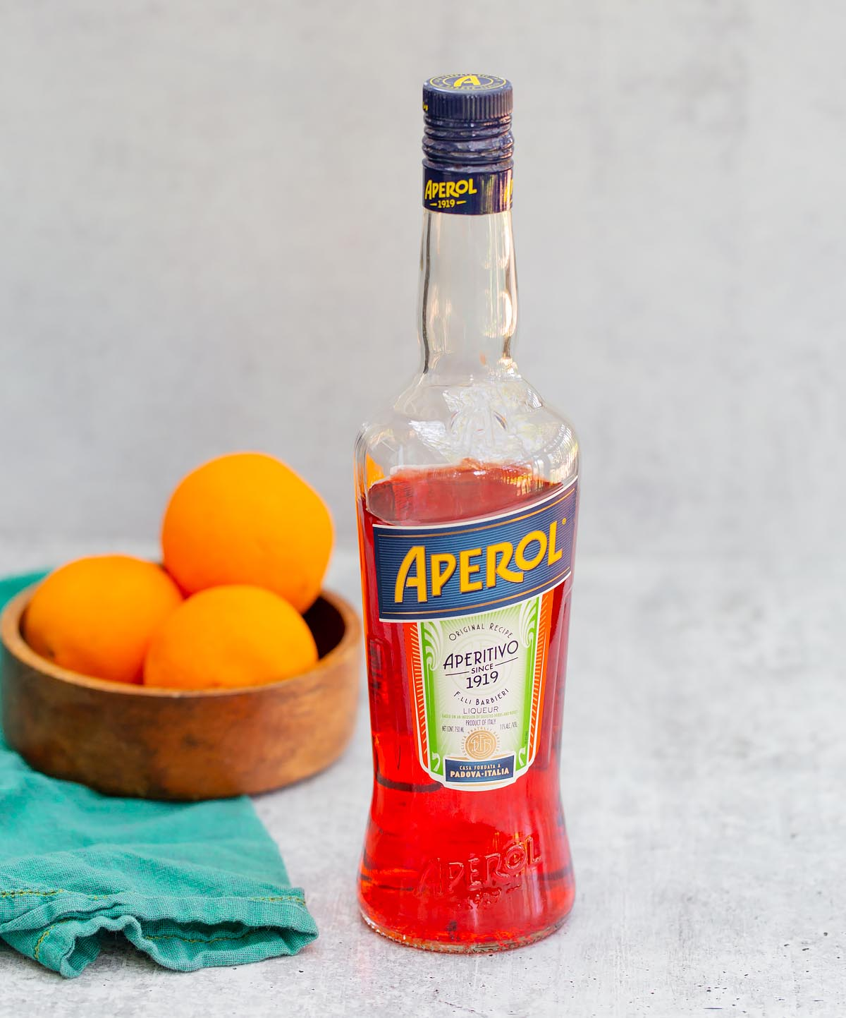 a bottle of aperol with a bowl of oranges in the background