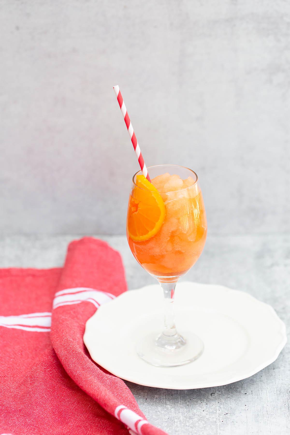 frozen aperol spritz with a straw