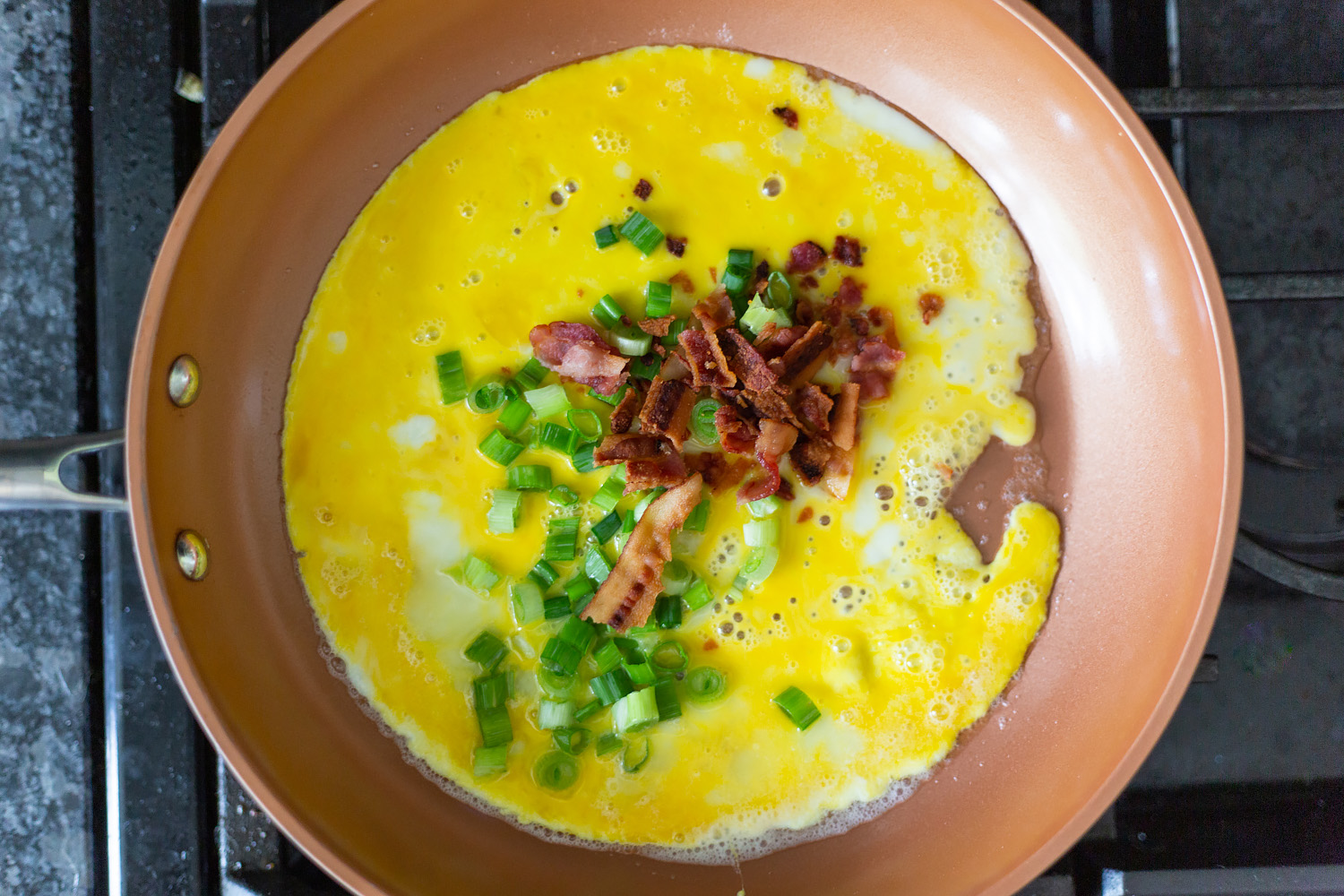cooking eggs, bacon, and green onions