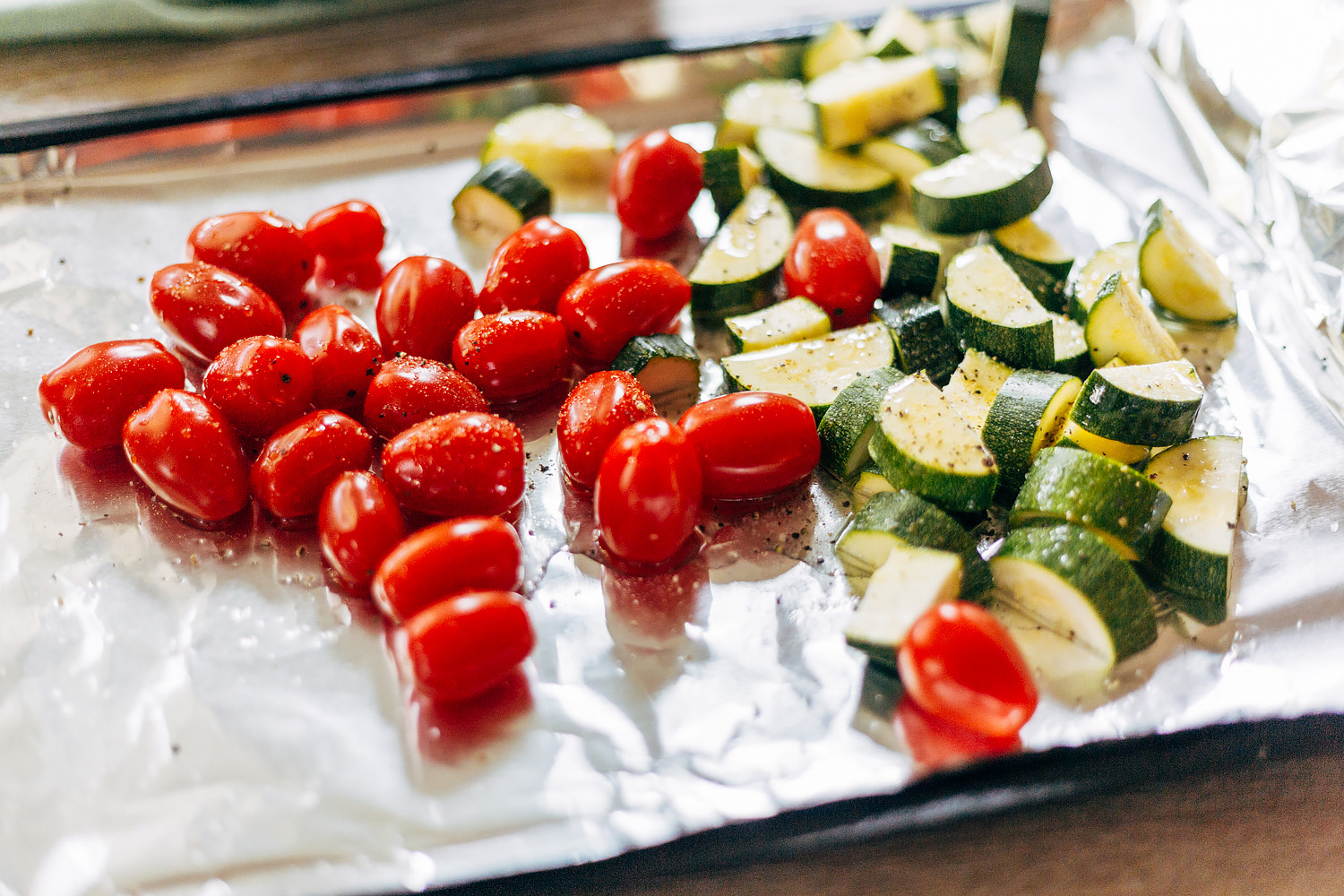 zucchini and tomatoes on a baking sheet