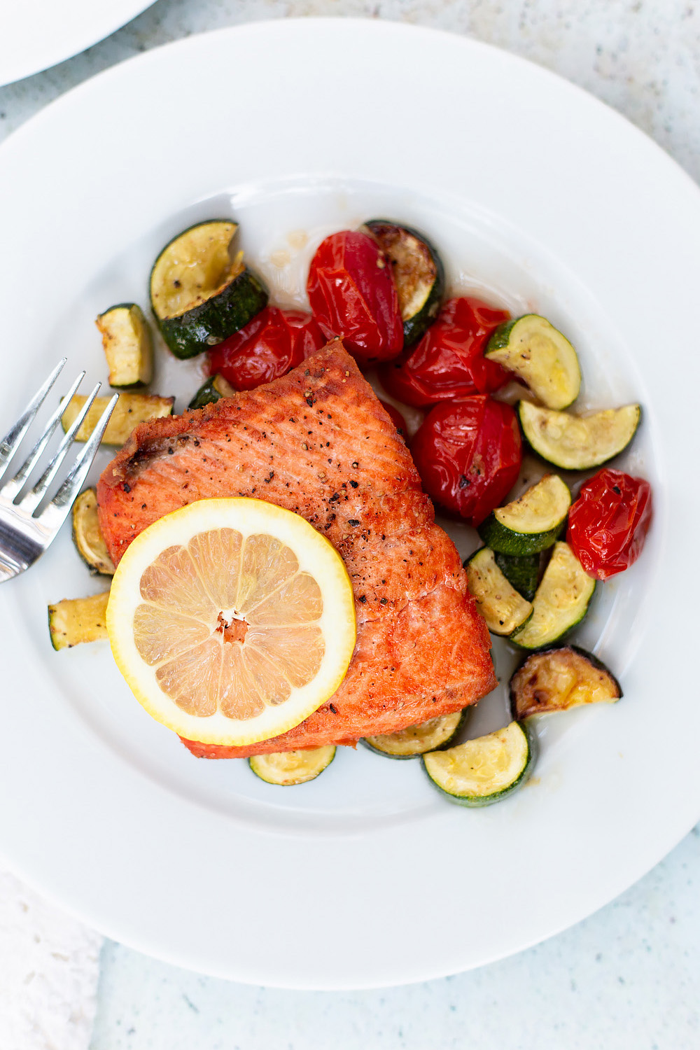 salmon with roasted veggies and a lemon slice