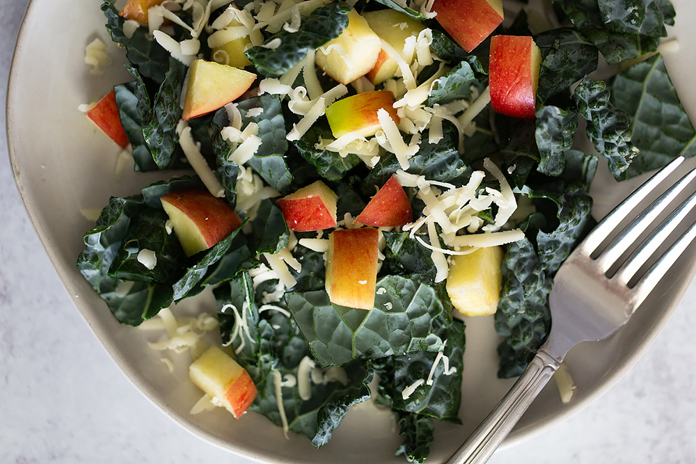 tuscan kale salad with apples and cheese with a fork
