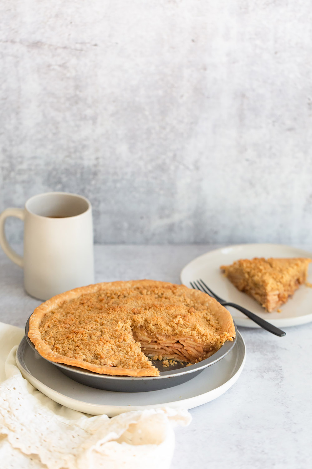 apple pie in a pie tin with a slice cut out
