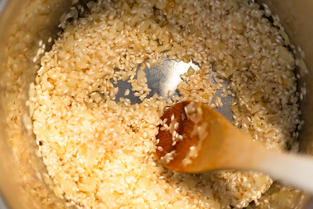 stirring arborio rice for parmesan risotto