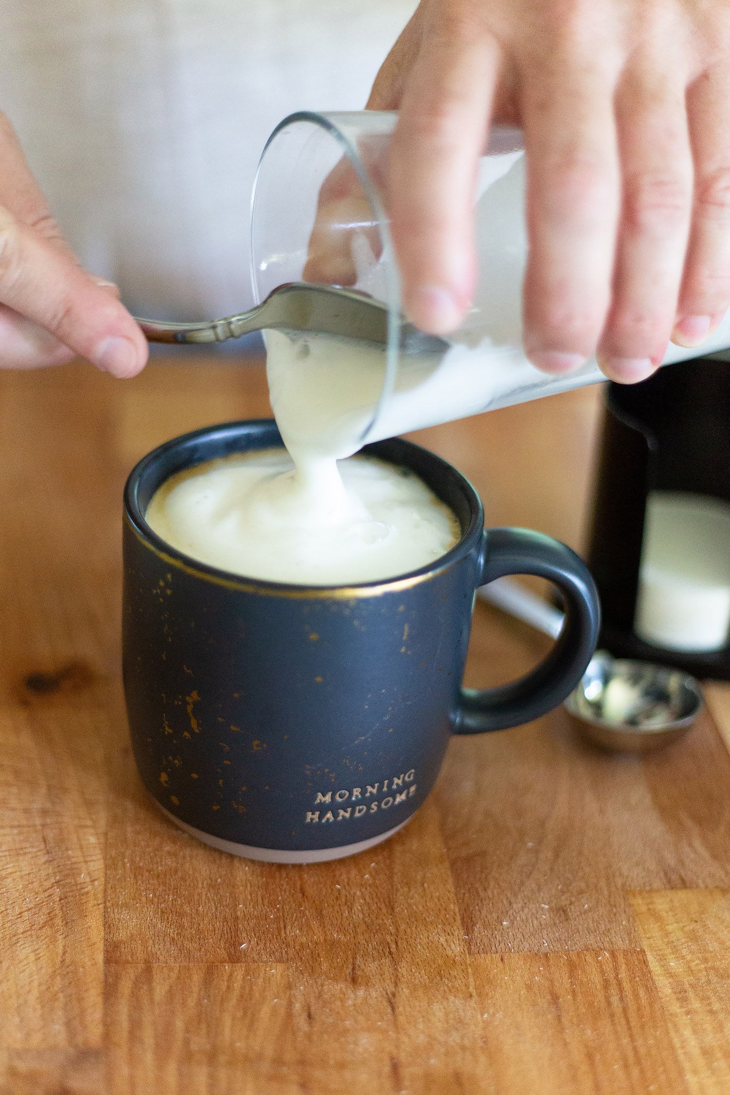 adding foamed milk to a cappuccino