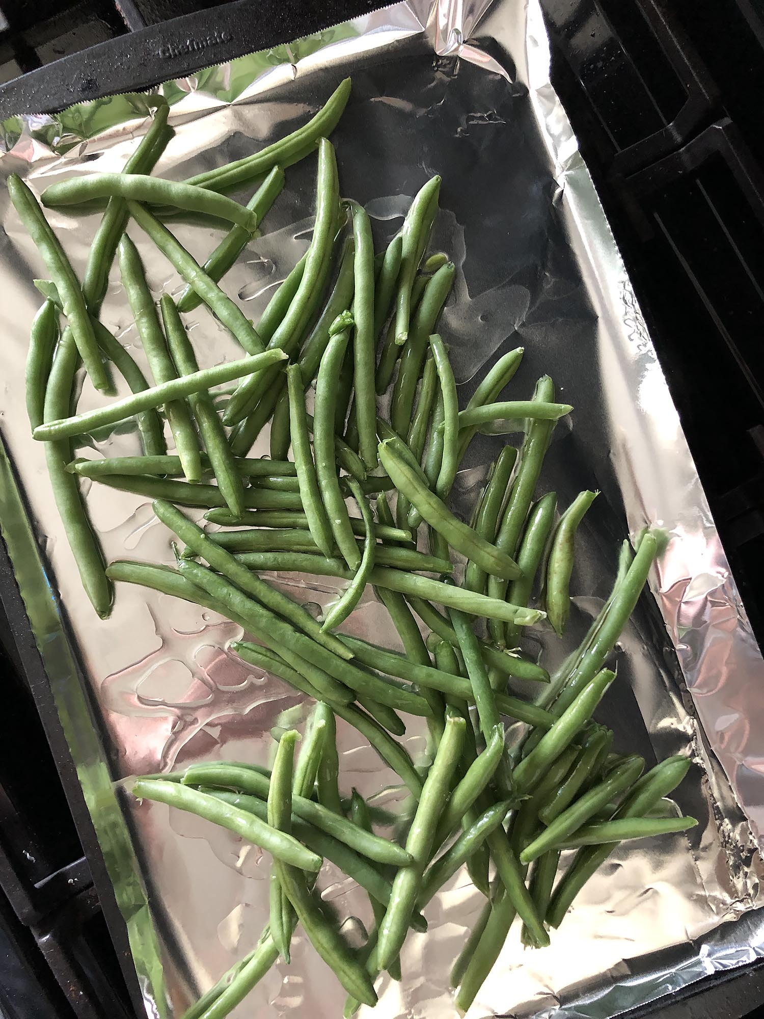 green beans on a foil lined baking sheet