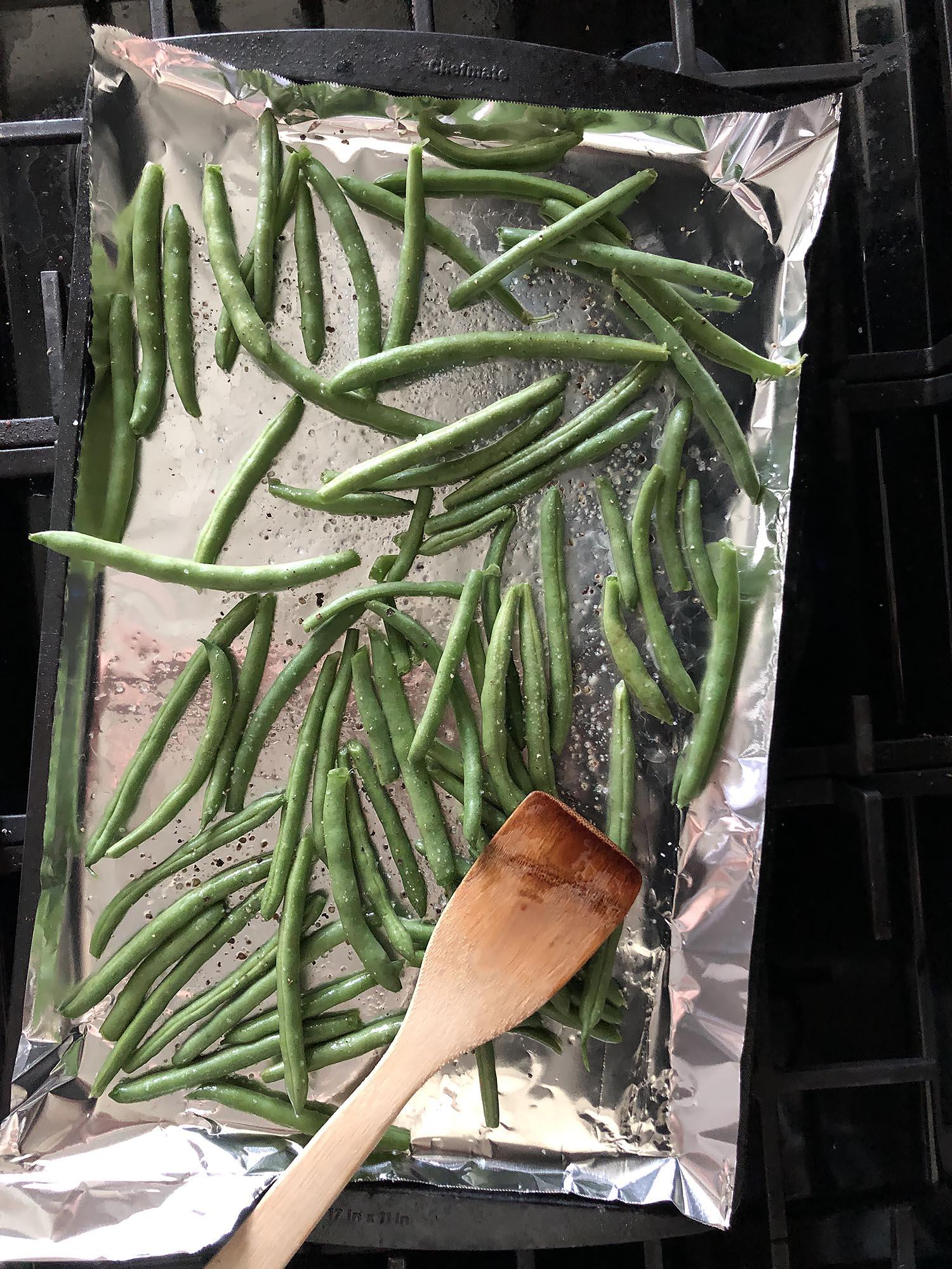 seasoned green beans on a baking sheet
