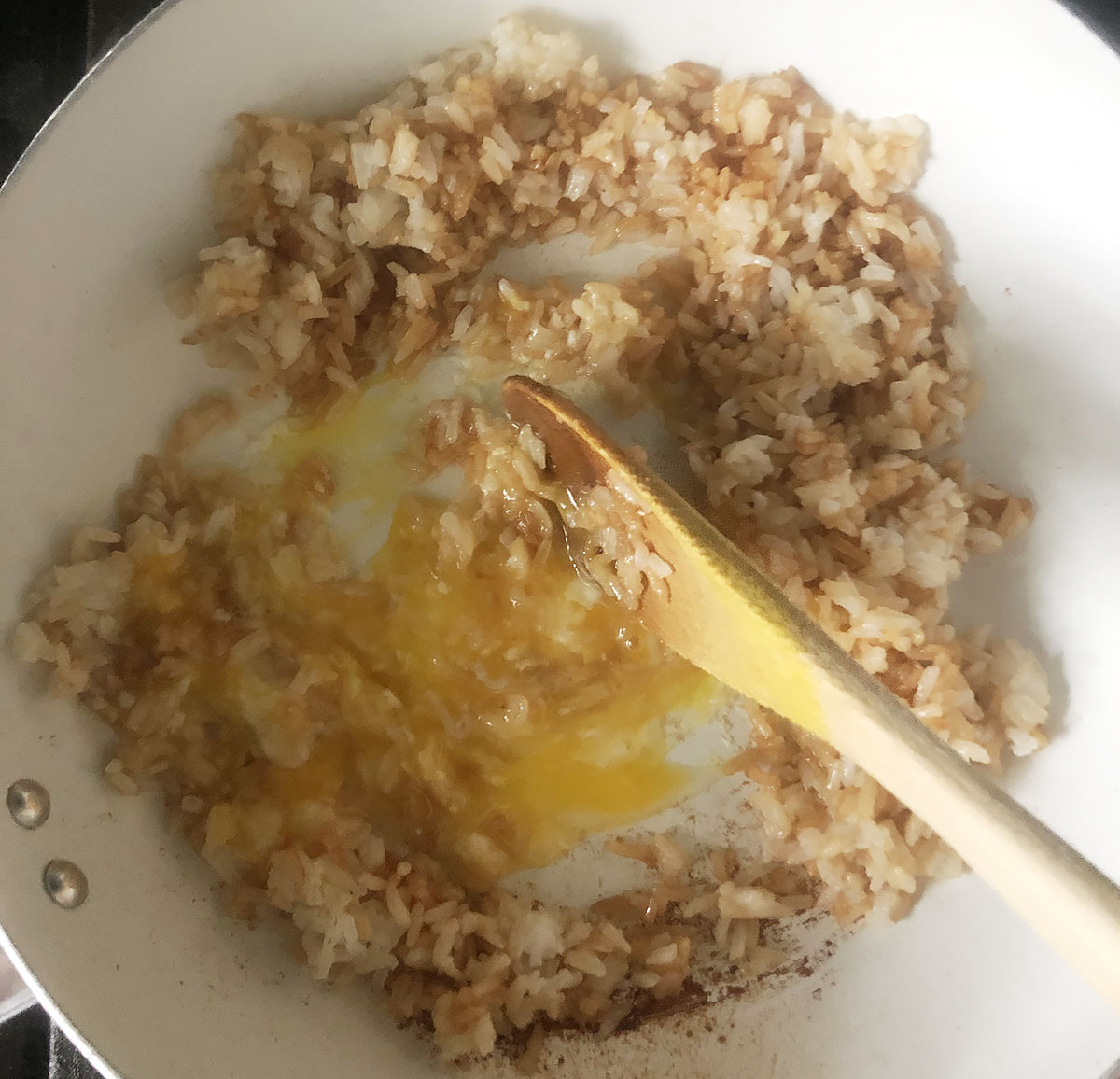 stirring an egg into fried rice