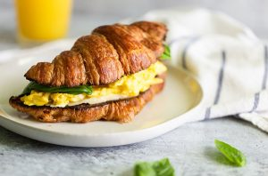 croissant breakfast sandwich with eggs and basil