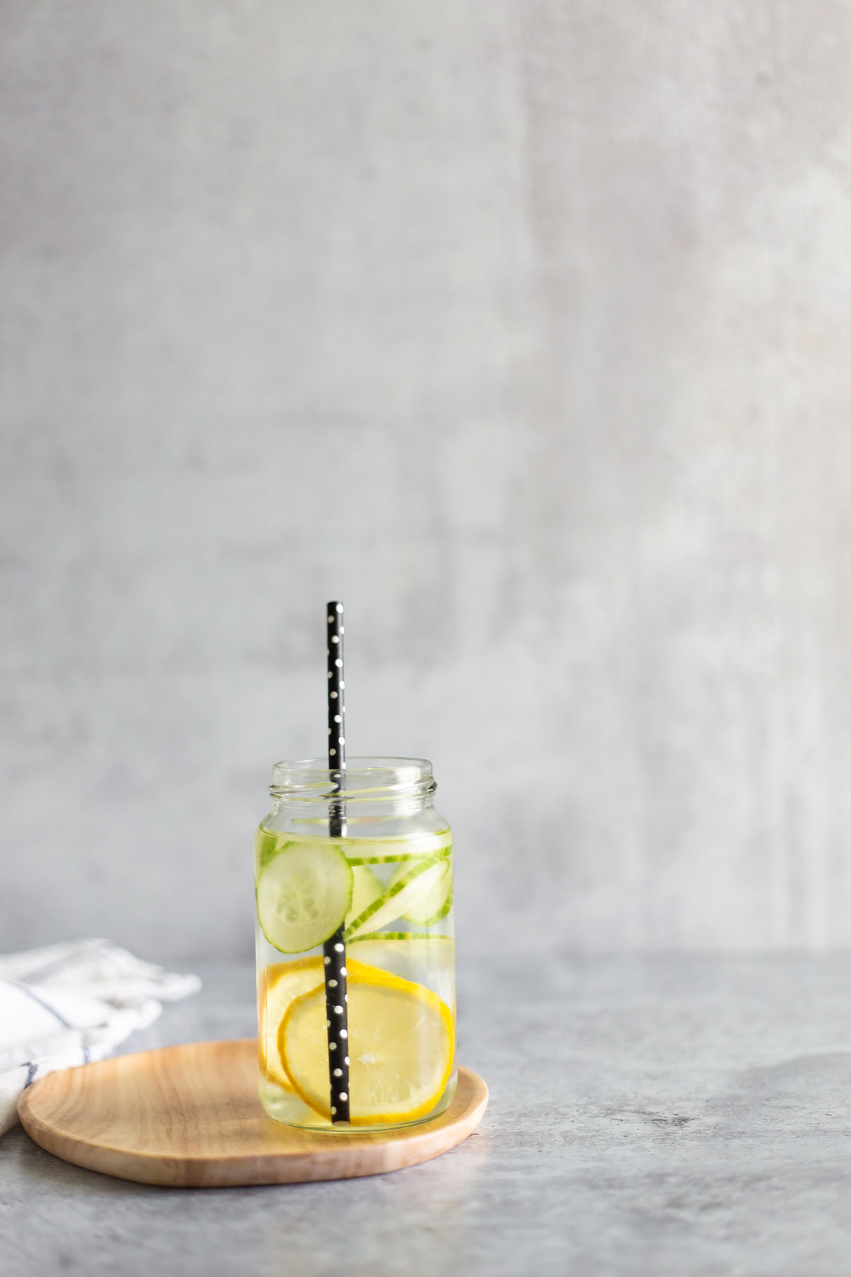 cucumbers and lemons in a jar with water and a straw