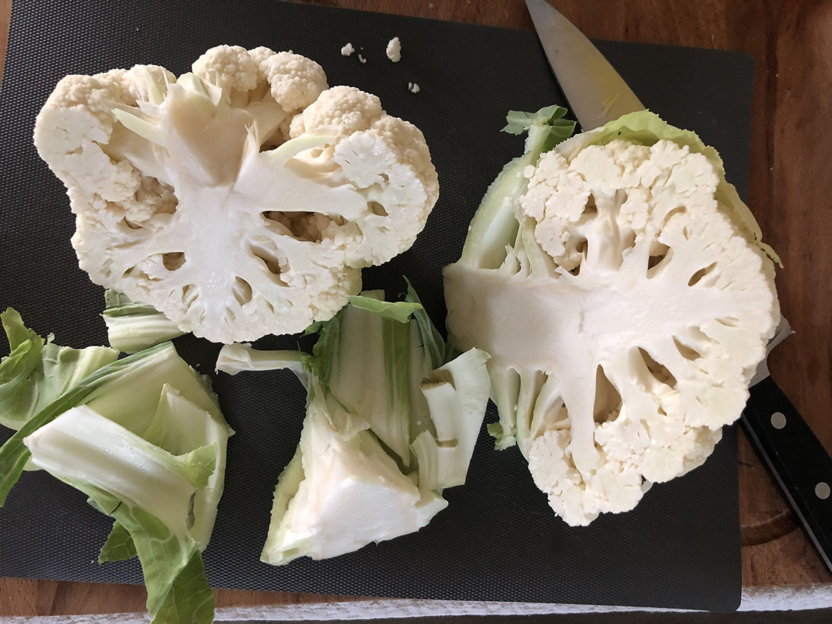 head of cauliflower being cut