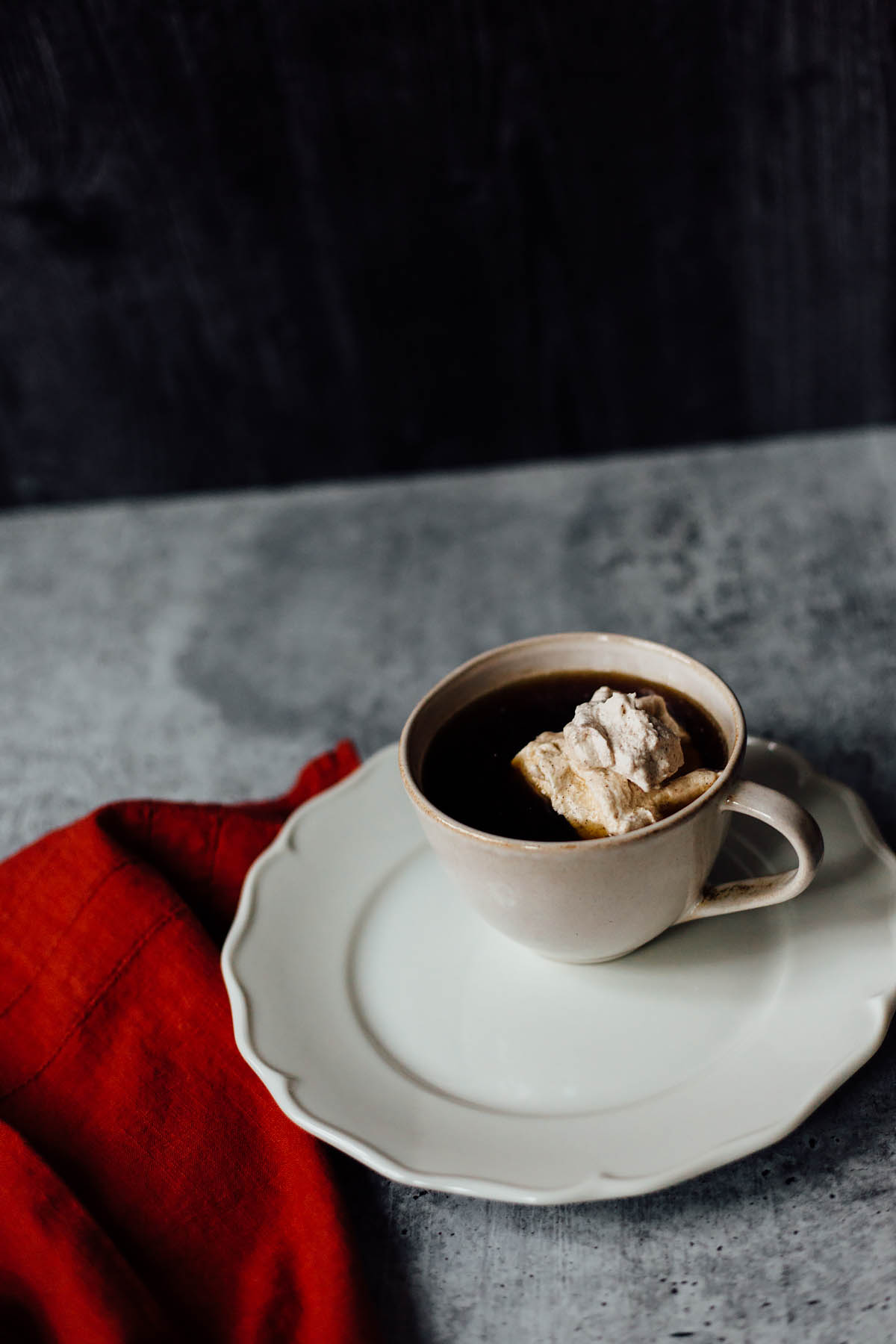 cinnamon whipped cream in coffee with a towel on the side