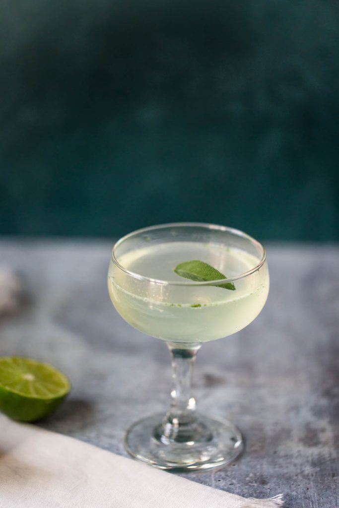 sage lime mocktail topped with a sage leaf in a coupe glass