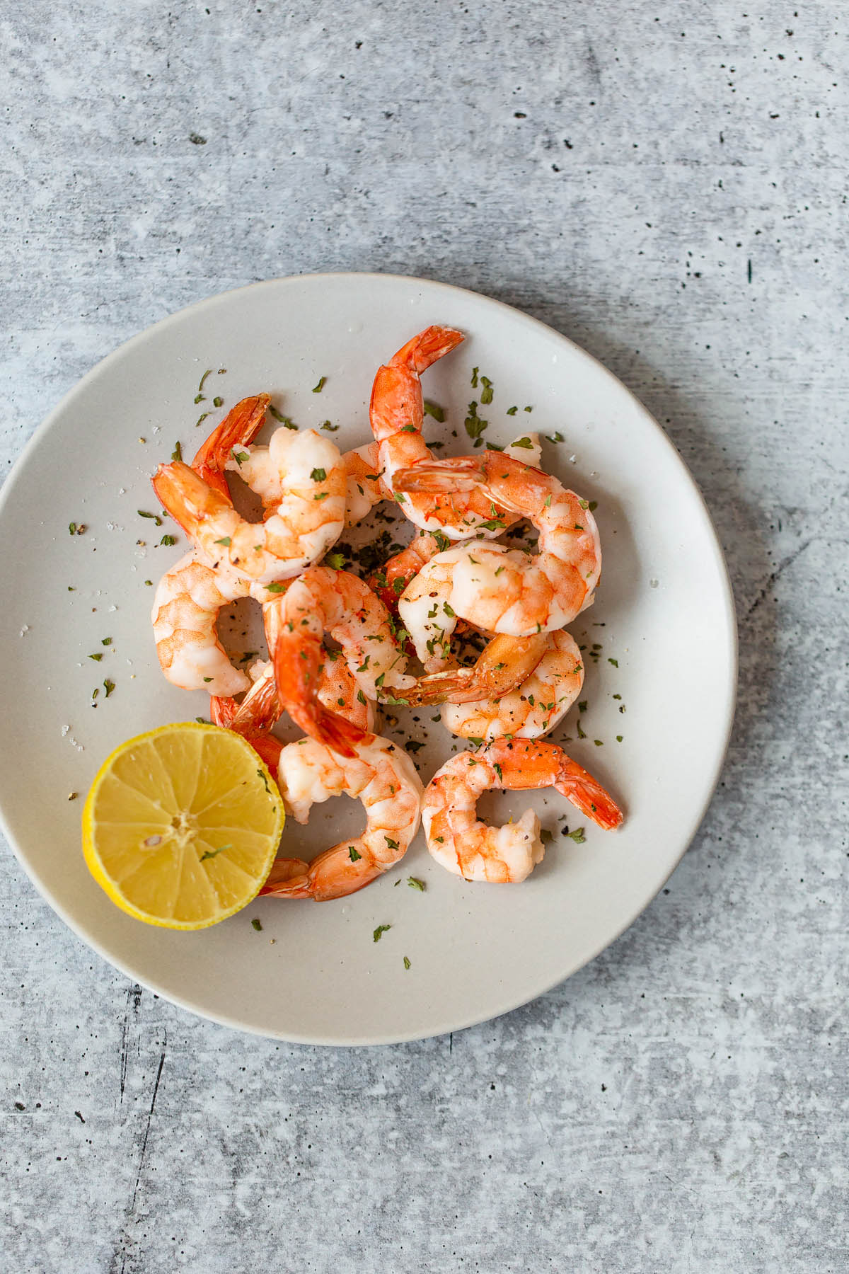 cooked shrimp on a plate with a lemon half