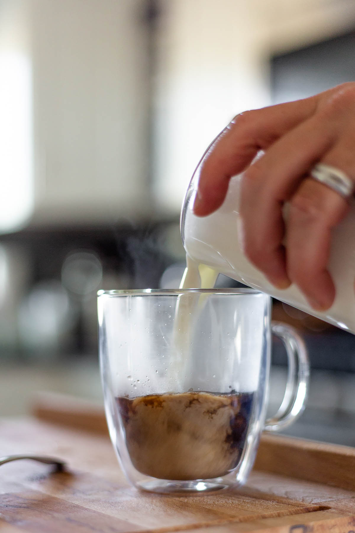 adding milk to a latte