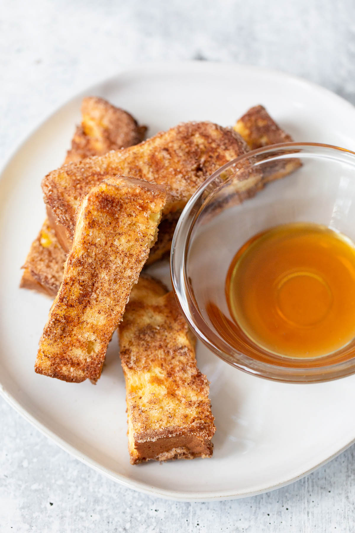 air fryer french toast sticks with a side of syrup