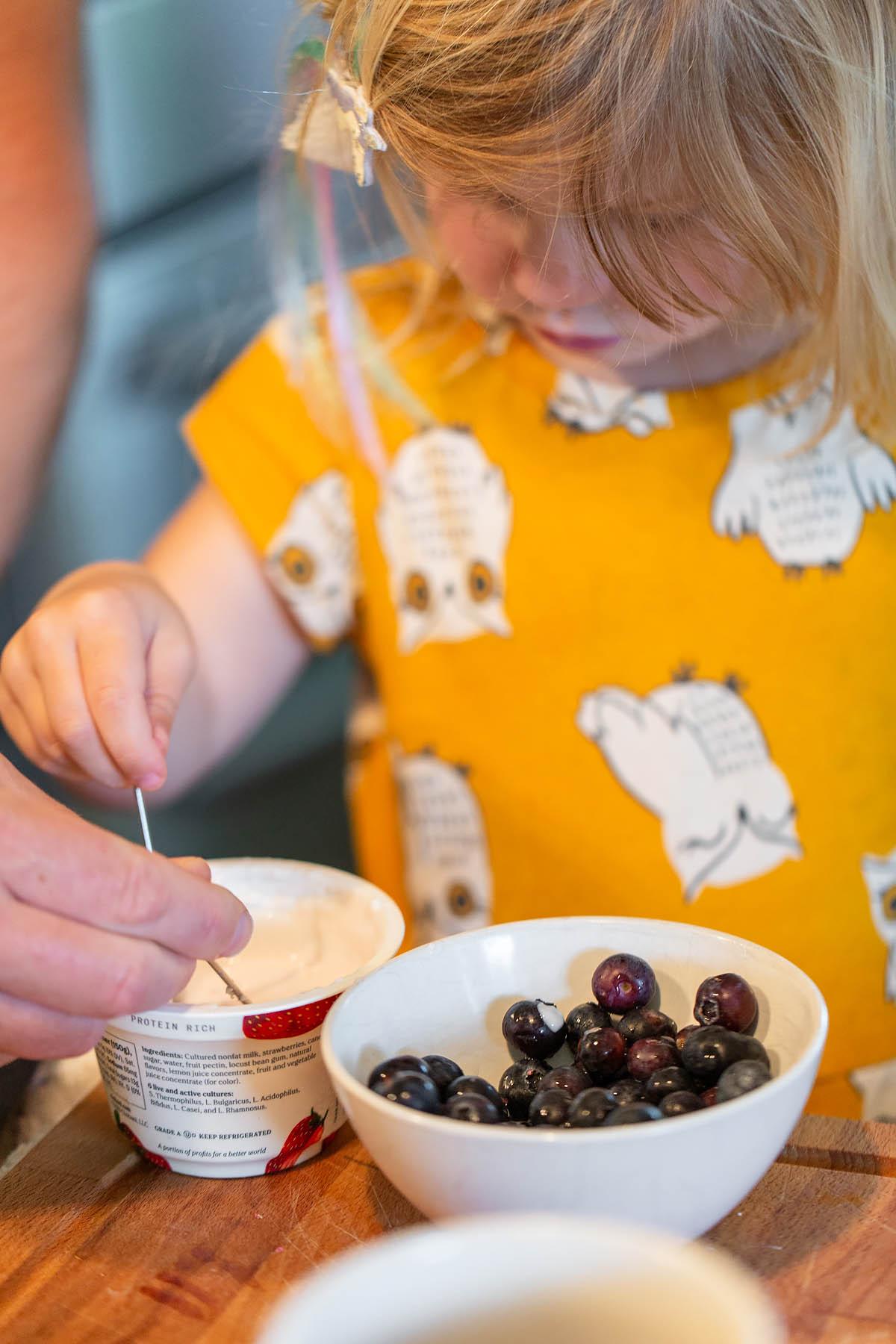 dipping blueberries into greek yogurt