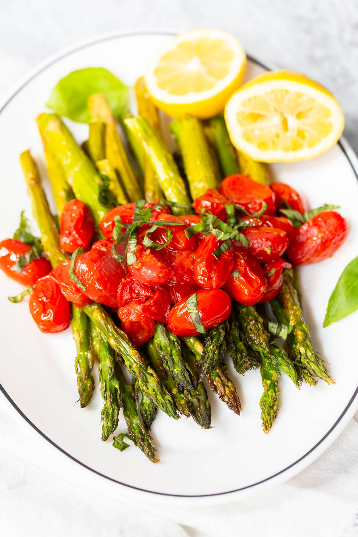 roasted asparagus and blistered cherry tomatoes with fresh basil on top