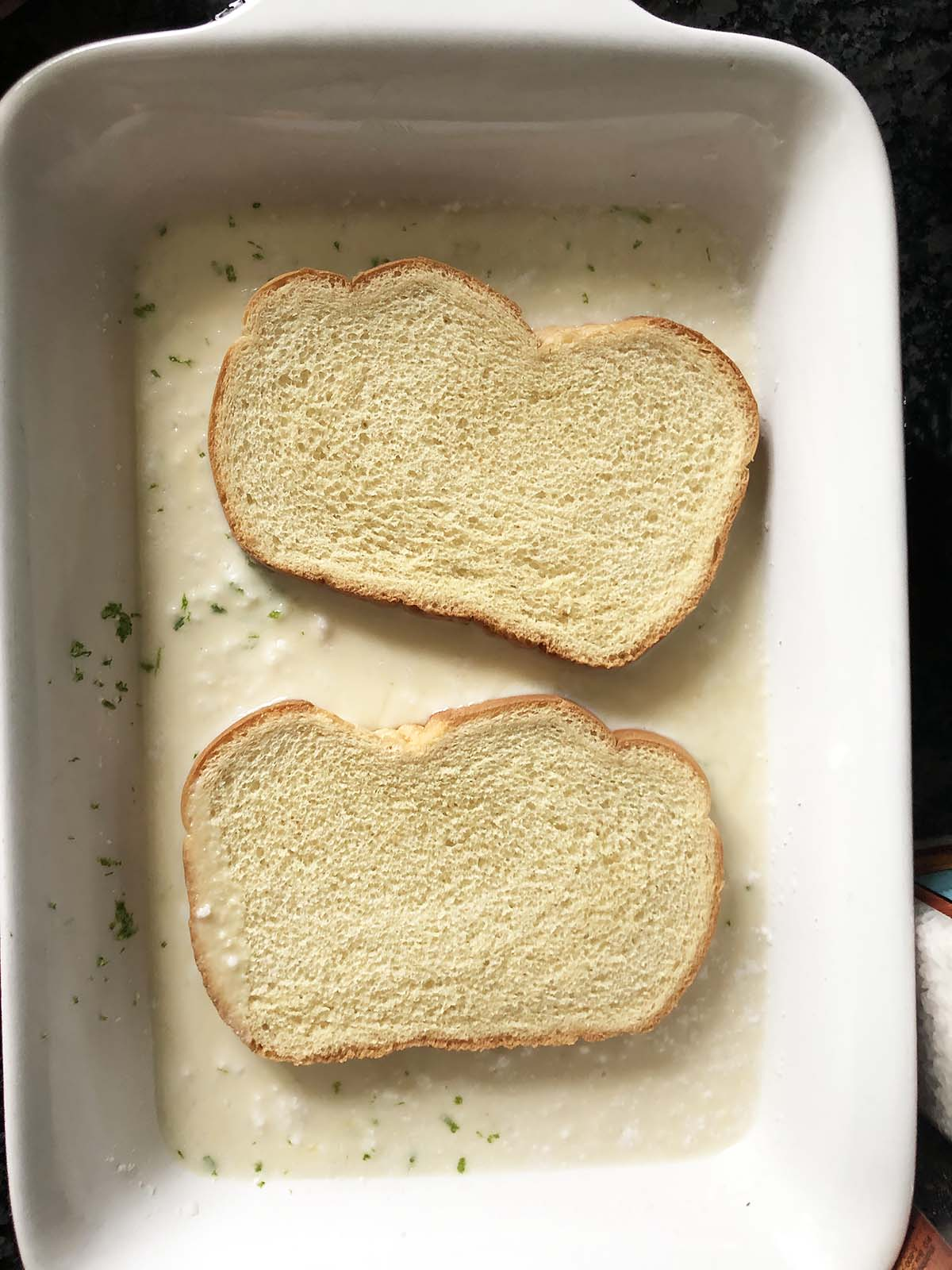 two slices of bread soaking in french toast batter