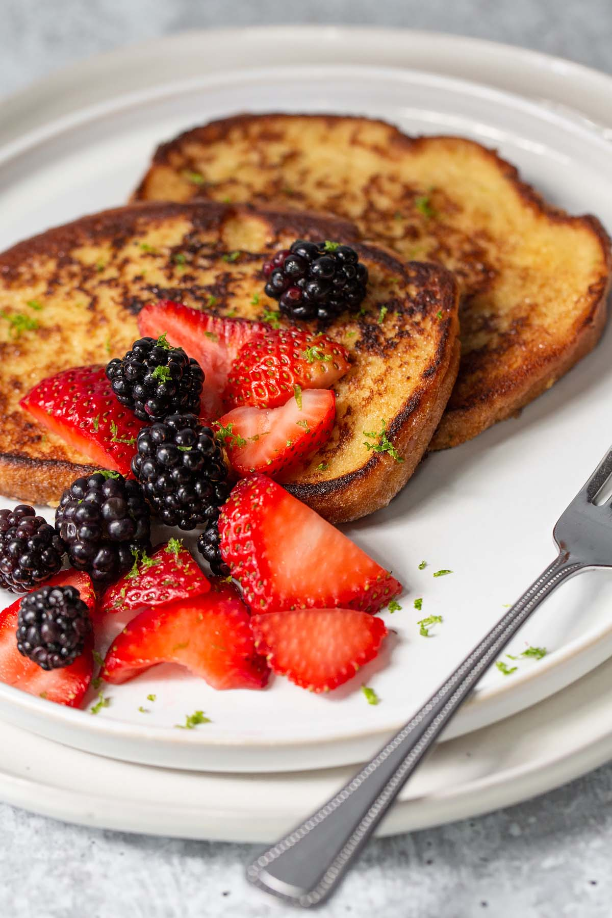 french toast topped with blackberries and sliced strawberries