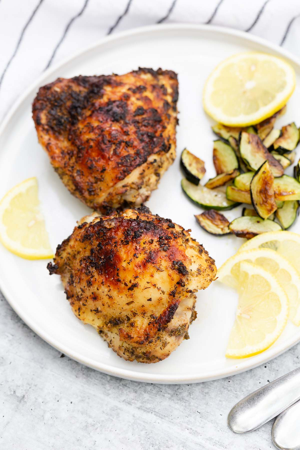 greek chicken thighs with lemon slices and cooked zucchini slices