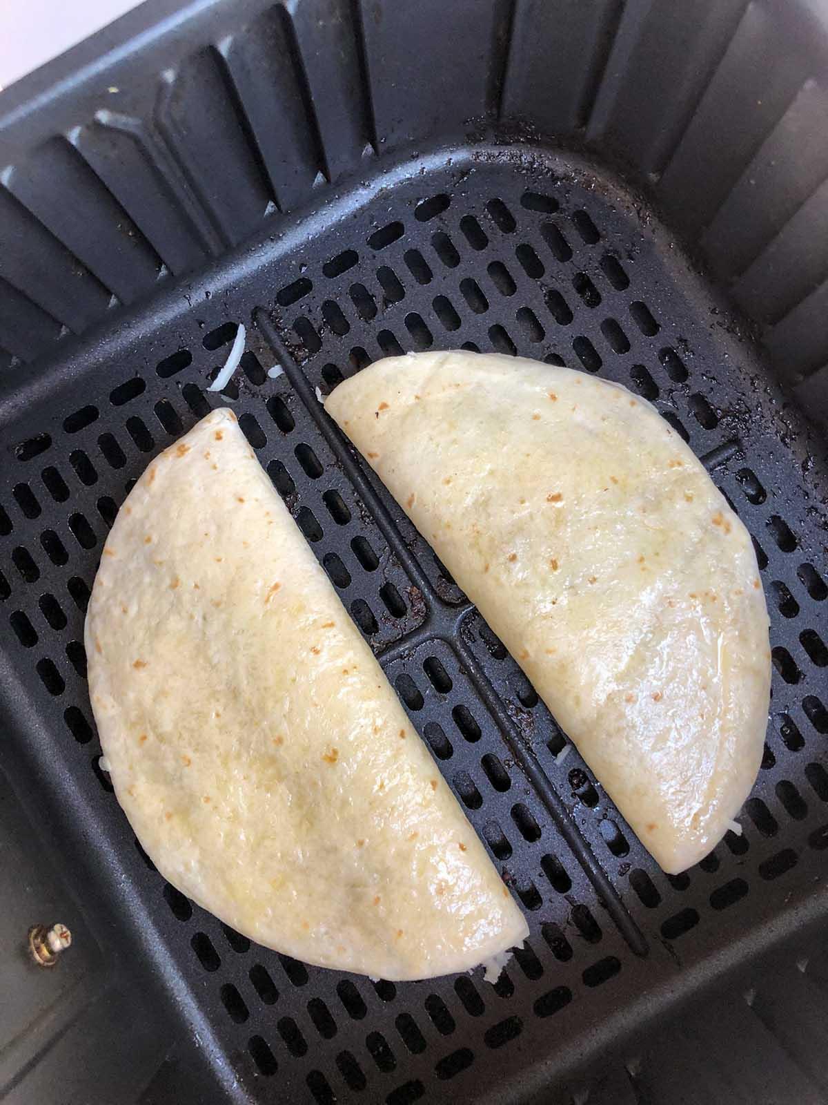 uncooked quesadilla in air fryer basket