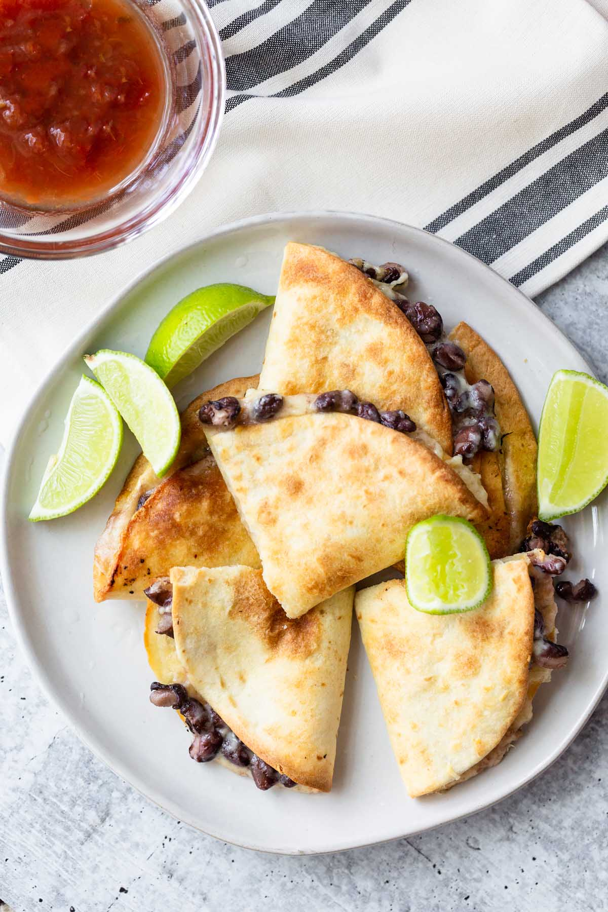 quesadillas on a plate with lime wedges