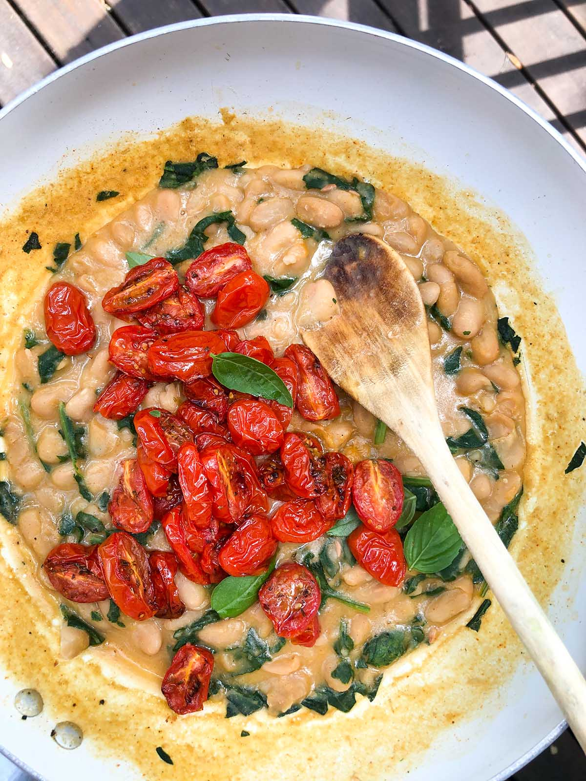 roasted tomatoes on top of cooked white beans in a skillet